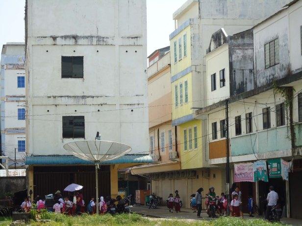 Sejumlah pelajar SD berjalan di samping gedung yang dijadikan sangar burung walet yang ada di samping sekolahnya di Dabo, Senin (15/10). Entah karena sudah terbiasa atau tak menghiraukan, suara bising walet tak menjadi (Yusuf Hidayat / Batam Pos)