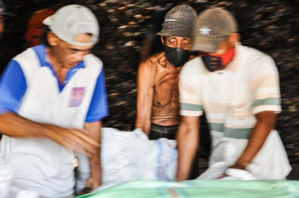 Old workers move a sack full of copra at a shed in Midai Village of Natuna Regecy, Indonesia on September 9, 2014. Copra become the second higest income for the village after clove.