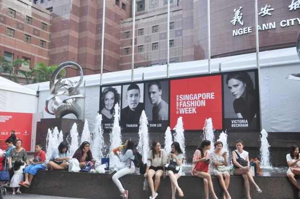 People sit in front of Singapore Fashion Week billboard at Orchard Road, Singapore on May 16,2015. Orchard Road is one of the most famous tourist destination in Singapore.