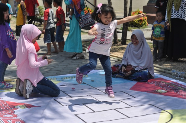 A girl jumps on the squares as she plays dende-dende at Traditional Games Festival in Makassar, Indonesia on October 18,2015. This festival was held to introduce kinds of traditional games played by Makassar kids in the past. Many traditional games in Indonesia have been dissapeared in this modern world due to the advancement of technology that offer many games through cellphones and video games. Most of Indonesian traditional games are physical games that can improve child psychomotor learning.