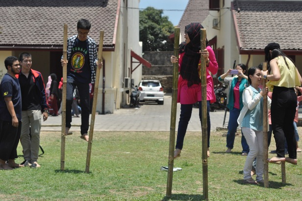 Indonesian teenagers take steps using traditional toy mallongga or stilt at Traditional Games Festival in Makassar, Indonesia on October 18,2015. This festival was held to introduce kinds of traditional games played by Makassar kids in the past. Many traditional games in Indonesia have been dissapeared in this modern world due to the advancement of technology that offer many games through cellphones and video games. Most of Indonesian traditional games are physical games that can improve child psychomotor learning.