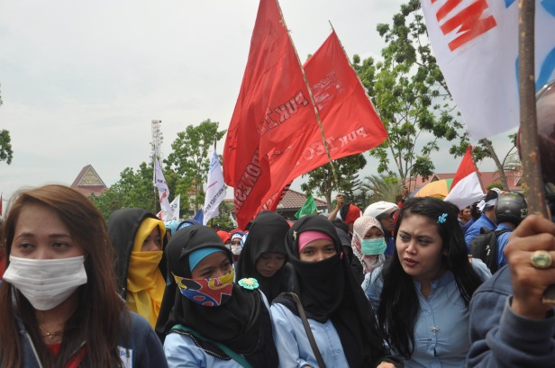Workers walking and waving flags after Labour Rally in Batam, Indonesia on May 1, 2015. Thousands of Indonesian workers gathered in front of the Mayor's office to attend a rally commemorating International Workers' Day in Batam, Riau Islands. They demanded that local government pay more attention to workers' welfare.