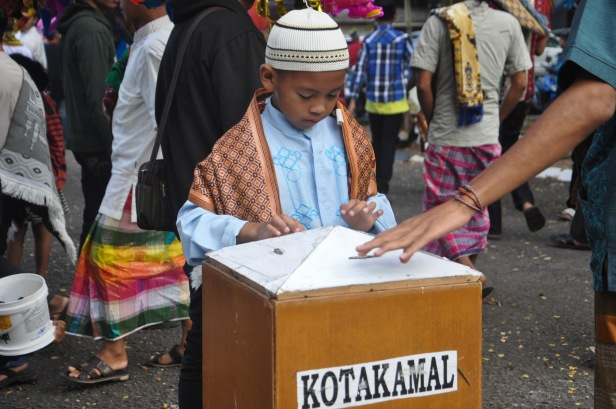 A kid inserted money into a donation box after Eid Al-Fitr prayer in Makassar, Indonesia on July 17, 2015.
