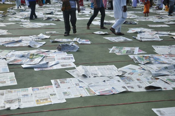 Prayer attendand left sheets of newspaper they used during Eid Al-Fitr prayer in Makassar on July 17, 2015.