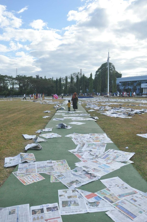 A mother and her son walking on the sheets of newspaper that used during Eid-Al Fitr in Makassar, Indonesia o July 17, 2015