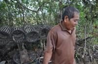 Salah satu warga di Pulau Galang dengan alat penangkap ikan tradisional di belakangnya.