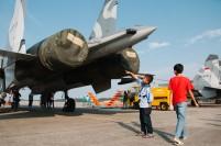 Seorang anak penasaran dengan pesawat tempur yang diparkir di Bandara Hang Nadim.