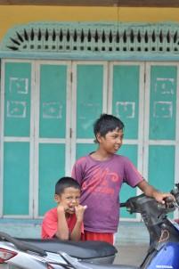 Dua anak laki-laki berpose di depan rumah tua di Pulau Midai, Natuna