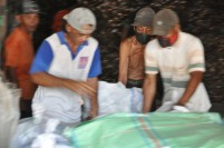 Tiga pekerja mengangkat karung penuh kopra di sebuah gudang penyimpanan kopra di Midai, Natuna