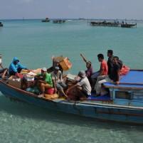 Warga pulau Midai menggunakan perahu bermesin kecil yang mengantar mereka ke ke kapal perintis Terigas yang buang sauh di lepas pantai.
