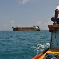 Perahu kayu tradisional bergerak ke arah kapal perintis Terigas yang buang sauh di lepas pantai Pulau Midai, Natuna.