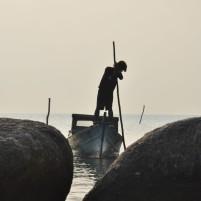 Nelayan lokal menggerakkan perahu di perairan yang dangkal menggunakan bambu.
