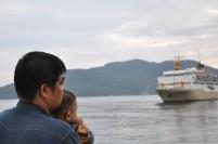 Seorang ayah mengendong anaknya menunggu KM Bukit Raya yang akan merapat di dermaga Selat Lampa