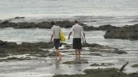 Dua orang peselancar berjalan menuju perairan di Teluk Dalam, Nias Utara.