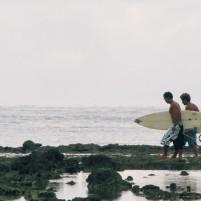 Dua peselancar berjalan menuju perairan di Teluk Dalam, Nias Selatan