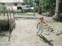 Seorang anak desa Lombozaua berlari di halaman rumah.