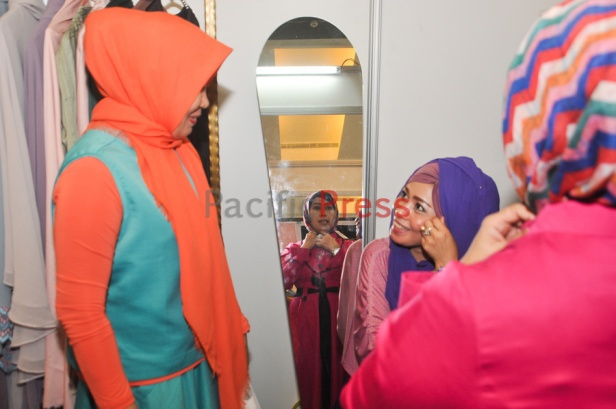 An Indonesian muslim woman fits a headscarf or hijab at Indonesia Moslem Fashion Expo. Muslim fashion Industry grows very fast in Indonesia in the past several years. As common fashion, Muslim clothing is changing consistently. Every year, there are many new designers and brands come.