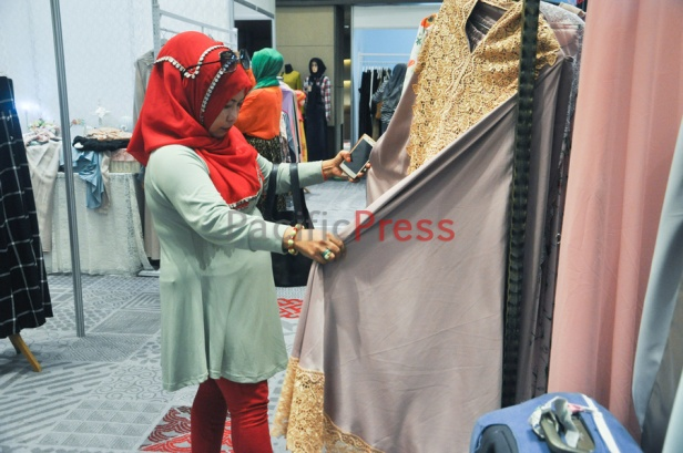 An Indonesian muslim woman picks the clothes at Indonesia Moslem Fashion Expo. Muslim fashion Industry grows very fast in Indonesia in the past several years. As common fashion, Muslim clothing is changing consistently. Every year, there are many new designers and brands come.