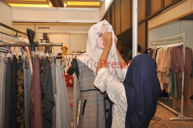 A woman wears a headscarf or hijab to a female mannequin at Indonesia Moslem Fashion Expo. Muslim fashion Industry grows very fast in Indonesia in the past several years. As common fashion, Muslim clothing is changing consistently. Every year, there are many new designers and brands come.
