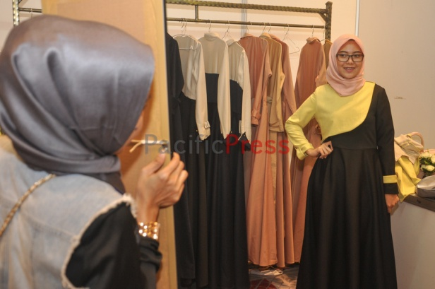 An Indonesian muslim woman fits a clothe at Indonesia Moslem Fashion Expo. Muslim fashion Industry grows very fast in Indonesia in the past several years. As common fashion, Muslim clothing is changing consistently. Every year, there are many new designers and brands come.
