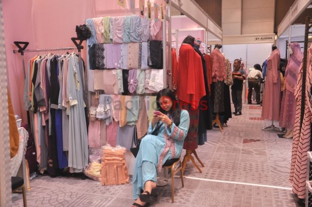 A booth keeper checks her phone at Indonesia Moslem Fashion Expo. Muslim fashion Industry grows very fast in Indonesia in the past several years. As common fashion, Muslim clothing is changing consistently. Every year, there are many new designers and brands come.