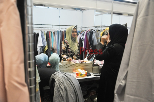 An Indonesian muslim woman visits a booth at Indonesia Moslem Fashion Expo. Muslim fashion Industry grows very fast in Indonesia in the past several years. As common fashion, Muslim clothing is changing consistently. Every year, there are many new designers and brands come.