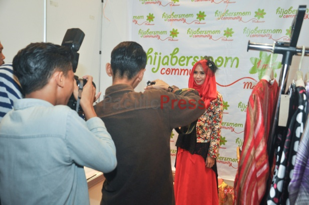 An Indonesian woman stands on a photo booth at Indonesia Moslem Fashion Expo. Muslim fashion Industry grows very fast in Indonesia in the past several years. As common fashion, Muslim clothing is changing consistently. Every year, there are many new designers and brands come.