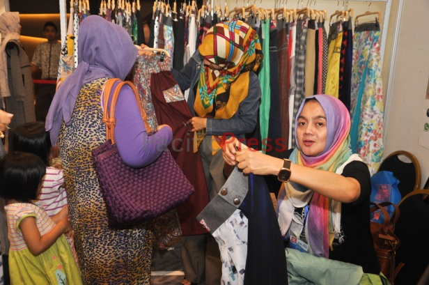 Indonesian muslim women pick clothes at Indonesia Moslem Fashion Expo. Muslim fashion Industry grows very fast in Indonesia in the past several years. As common fashion, Muslim clothing is changing consistently. Every year, there are many new designers and brands come.