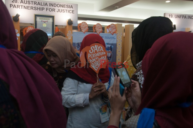 A woman covers her face with a hand fan with anti corruption message at Eastern Indonesia Forum Festival. The festival was attended by many civil societies and NGOs from many areas in Eastern Indonesia and became an event to display and study achievement of many smart practices done by local communities based on their local wisdom in order to improve their welfare.