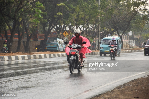MAKASSAR, SOUTH SULAWESI, INDONESIA - 2015/10/31: Motorcycle rider wearing a poncho to cover himself from the rain. Heavy rain hit the city after four dry months. (Photo by Yermia Riezky Santiag/Pacific Press/LightRocket via Getty Images)