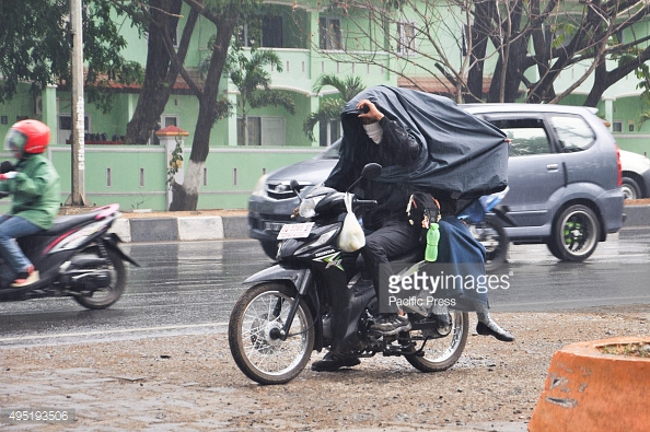 MAKASSAR, SOUTH SULAWESI, INDONESIA - 2015/10/31: Motorcycle riders try to cover themself from rain in Kapasa Village. Heavy rain hit the city after four dry months. (Photo by Yermia Riezky Santiag/Pacific Press/LightRocket via Getty Images)