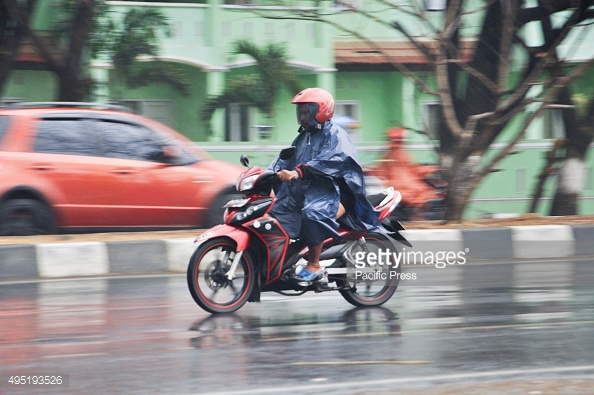 MAKASSAR, SOUTH SULAWESI, INDONESIA - 2015/10/31: Motorcycle rider wears a poncho to cover himself from the rain. Heavy rain hit the city after four dry months. (Photo by Yermia Riezky Santiag/Pacific Press/LightRocket via Getty Images)
