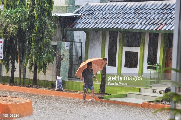 MAKASSAR, SOUTH SULAWESI, INDONESIA - 2015/10/31: A man walks under an umbrella through the rain in Kapasa. Heavy rain hits the city after four dry months. (Photo by Yermia Riezky Santiag/Pacific Press/LightRocket via Getty Images)